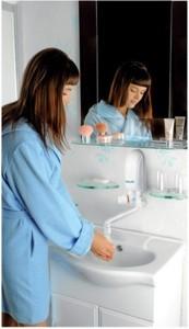 Podgrzewacz dafi zamontowany nad zlewem i kobieta myjąca ręce